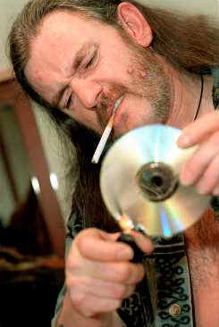 FIREPOWER: With his cigarette properly lit, Lemmy turns his attention toward recycling the latest Nicki Minaj CD into something more useful. Like an ashtray. Or a toenail scraper.